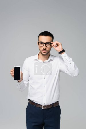 Photo for Hispanic manager adjusting eyeglasses while showing cellphone with blank screen isolated on grey - Royalty Free Image