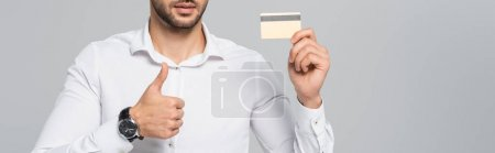 cropped view of manager with credit card showing thumb up isolated on grey, banner