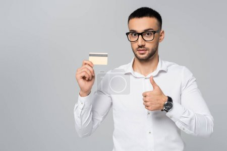 young hispanic businessman showing thumb up while holding credit card isolated on grey