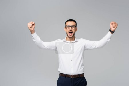 Photo for Excited hispanic businessman showing success gesture and shouting isolated on grey - Royalty Free Image