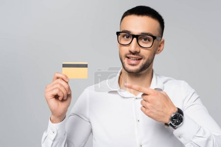 smiling hispanic businessman pointing with finger at credit card isolated on grey