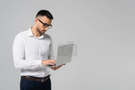 Photo for Young hispanic manager in eyeglasses typing on laptop isolated on grey - Royalty Free Image