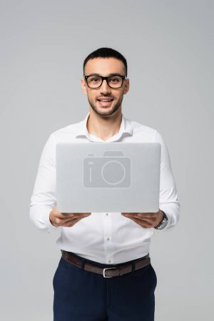 successful hispanic businessman holding laptop and looking at camera isolated on grey
