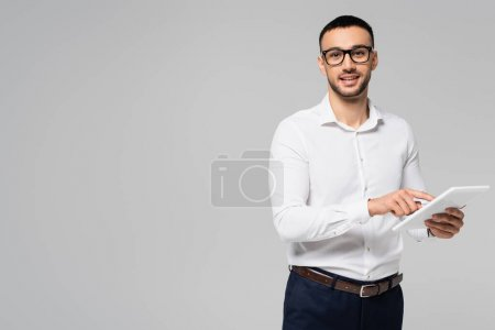 Photo pour Gestionnaire hispanique souriant en chemise blanche et lunettes à l'aide d'une tablette numérique isolée sur gris - image libre de droit