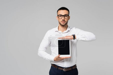 brunette hispanic businessman in eyeglasses showing digital tablet with blank screen isolated on grey