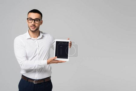 young hispanic businessman in white shirt holding digital tablet with blank screen isolated on grey