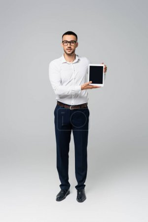 Photo for Full length view of hispanic businessman showing digital tablet with blank screen on grey - Royalty Free Image