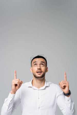 young hispanic businessman looking up and pointing with fingers isolated on grey