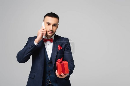 Photo for Brunette hispanic man in elegant suit talking on smartphone while holding red gift box isolated on grey - Royalty Free Image