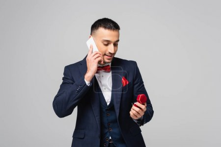 smiling hispanic man in blue suit talking on smartphone while holding jewelry box isolated on grey