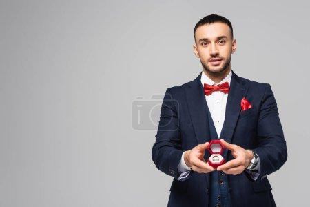 Photo pour Jeune homme hispanique en costume élégant tenant boîte à bijoux rouge avec anneau de mariage isolé sur gris - image libre de droit
