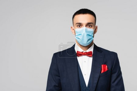 Photo for Young hispanic man in elegant blue suit and medical mask looking at camera isolated on grey - Royalty Free Image
