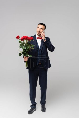 young hispanic man in elegant suit talking on smartphone while holding red roses on grey