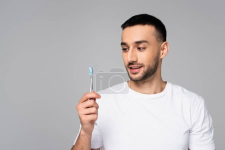 cheerful hispanic man in white t-shirt holding toothbrush isolated on grey