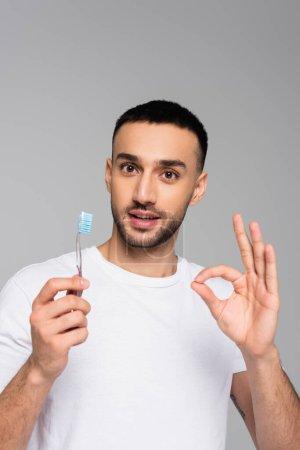 smiling hispanic man holding toothbrush while showing ok gesture isolated on grey