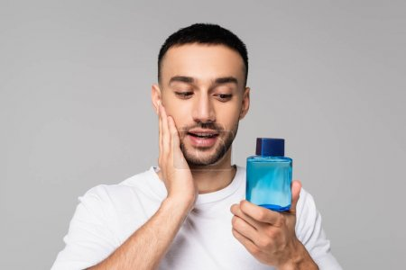 brunette hispanic man applying aftershave lotion on face isolated on grey