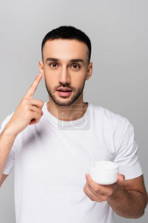 young hispanic man pointing applying face cream isolated on grey