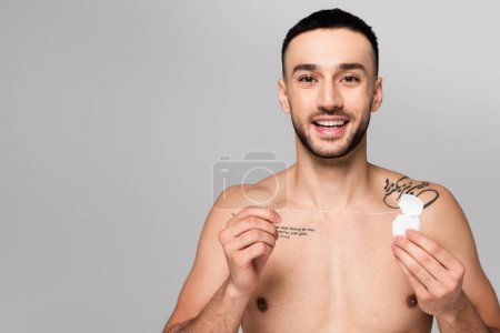 young shirtless hispanic man holding dental floss while looking at camera isolated on grey
