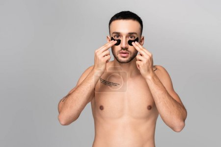 Photo for Young shirtless hispanic man applying eye patches isolated on grey - Royalty Free Image