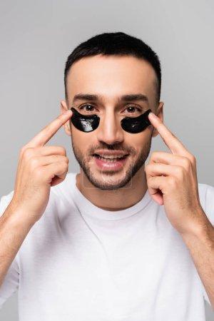smiling hispanic man applying eye patches isolated on grey