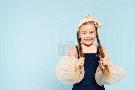Photo pour Enfant joyeux touchant des nattes et souriant isolé sur bleu - image libre de droit