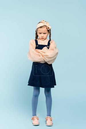 Photo for Full length of offended kid with pigtails standing with crossed arms on blue - Royalty Free Image