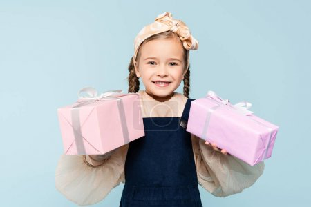 happy kid with pigtails holding presents isolated on blue