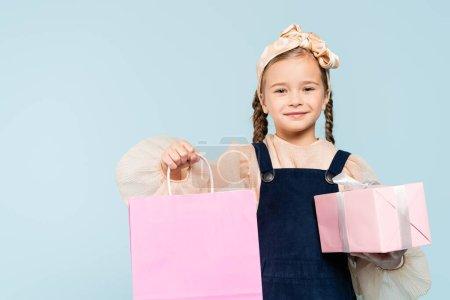 Photo pour Enfant heureux avec des nattes tenant sac à provisions et présent isolé sur bleu - image libre de droit