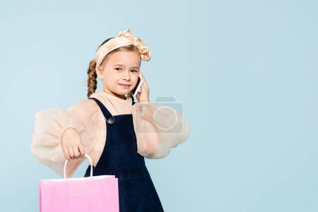 Photo for Happy kid with pigtails talking on smartphone and holding shopping bag isolated on blue - Royalty Free Image