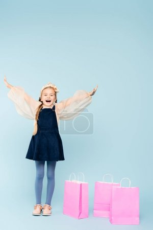 Photo for Full length of amazed little girl in dress standing with outstretched hands near shopping bags on blue - Royalty Free Image