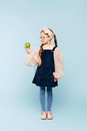 Photo for Full length of little girl in dress and glasses looking at green apple on blue - Royalty Free Image