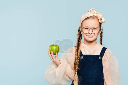 Photo for Smart kid in glasses holding green apple and smiling isolated on blue - Royalty Free Image