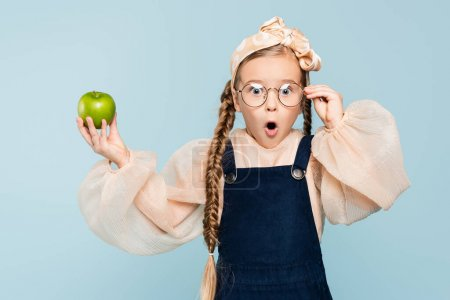 shocked kid adjusting glasses and holding green apple isolated on blue