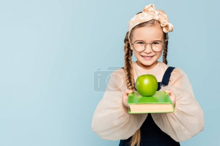 Photo for Smart kid in glasses holding book with green apple and smiling isolated on blue - Royalty Free Image