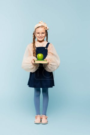 Photo for Full length of smart kid in glasses holding book and green apple on blue - Royalty Free Image