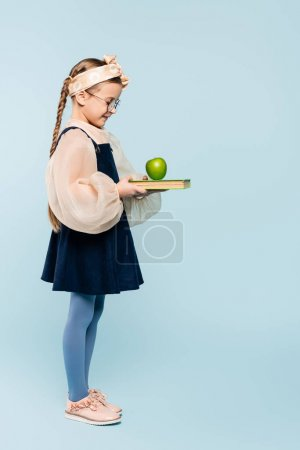 Photo for Full length of smart kid in glasses looking at book and green apple on blue - Royalty Free Image