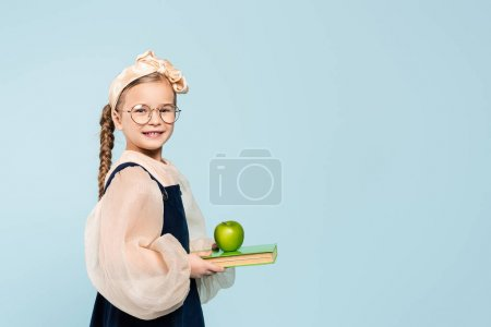 smart kid in glasses smiling while holding book and green apple isolated on blue
