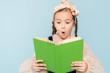 Photo for Shocked little girl with pigtails reading book isolated on blue - Royalty Free Image