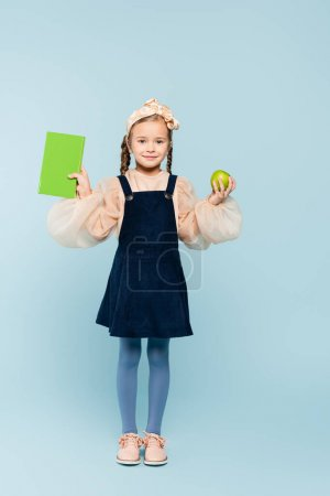 Photo for Full length of happy kid in dress holding book and green apple on blue - Royalty Free Image