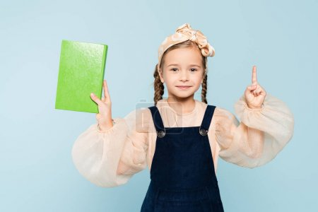 Photo for Little girl with pigtails holding book and pointing with finger isolated on blue - Royalty Free Image