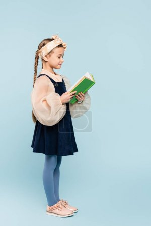 full length of little girl with pigtails reading book on blue