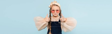 Photo for Little girl in sunglasses showing thumbs up isolated on blue, banner - Royalty Free Image