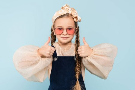 Photo for Little girl in sunglasses showing thumbs up isolated on blue - Royalty Free Image