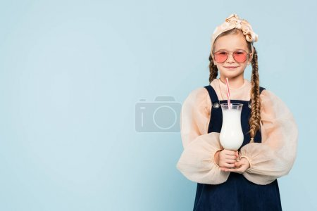 Photo for Cheerful girl in sunglasses holding glass with milkshake isolated on blue - Royalty Free Image