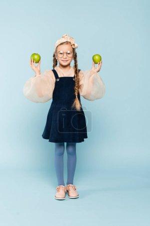 Photo pour Pleine longueur de gosse dans des lunettes tenant des pommes vertes sur bleu - image libre de droit