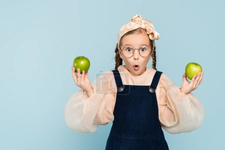 Photo for Surprised kid in glasses holding green apples isolated on blue - Royalty Free Image