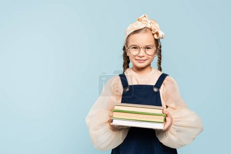 smart kid in glasses smiling while holding books isolated on blue
