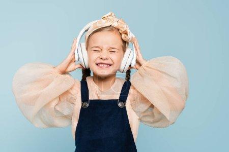 Photo pour Heureux enfant dans bandeau avec arc et écouteurs sans fil écouter de la musique isolée sur bleu - image libre de droit