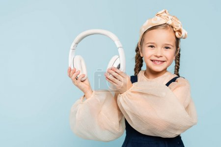 Photo for Cheerful kid in headband with bow holding wireless headphones isolated on blue - Royalty Free Image