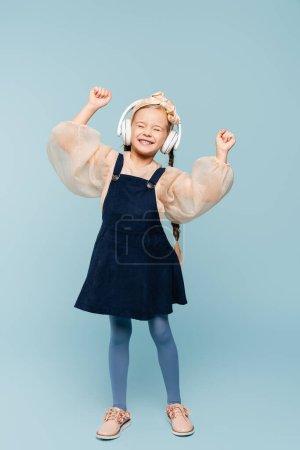 Photo pour Toute la longueur du gamin souriant dans le bandeau avec arc et écouteurs sans fil écouter de la musique sur bleu - image libre de droit